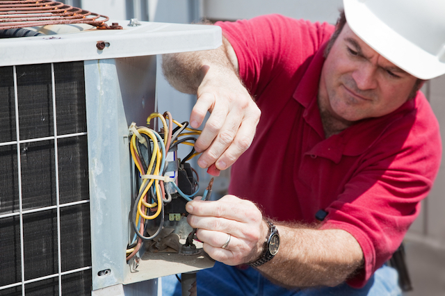 A close up of a caucasian male in a red polo shirt and white hard hat working on the wires of an outdoor HVAC unit