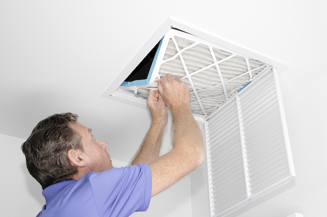 An adult male is changing the HVAC system filter in an air vent on a white ceiling.