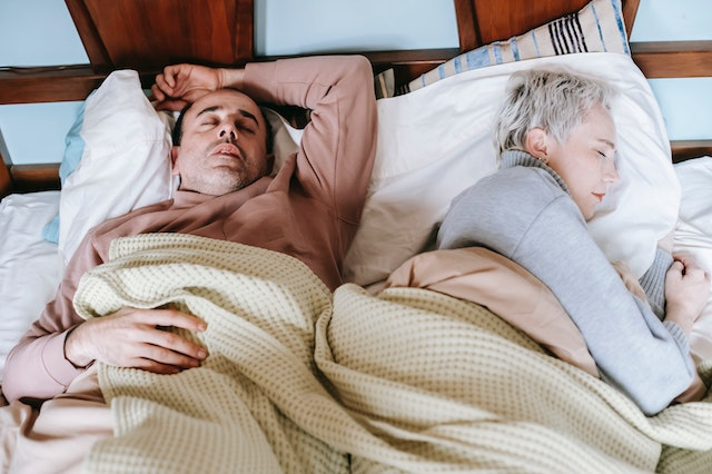 A couple sleeping in a bed. One person is comfortable and one is not.