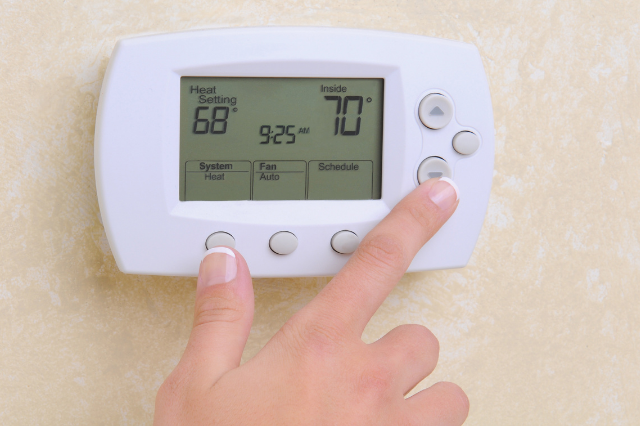 A person adjusting the temperature on a thermostat on the wall.