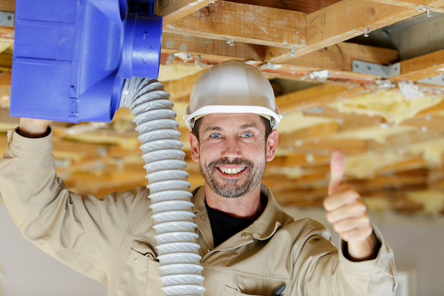 A male HVAC technician is installing an HVAC unit while looking at the camera, smiling, and giving a thumbs up gesture.